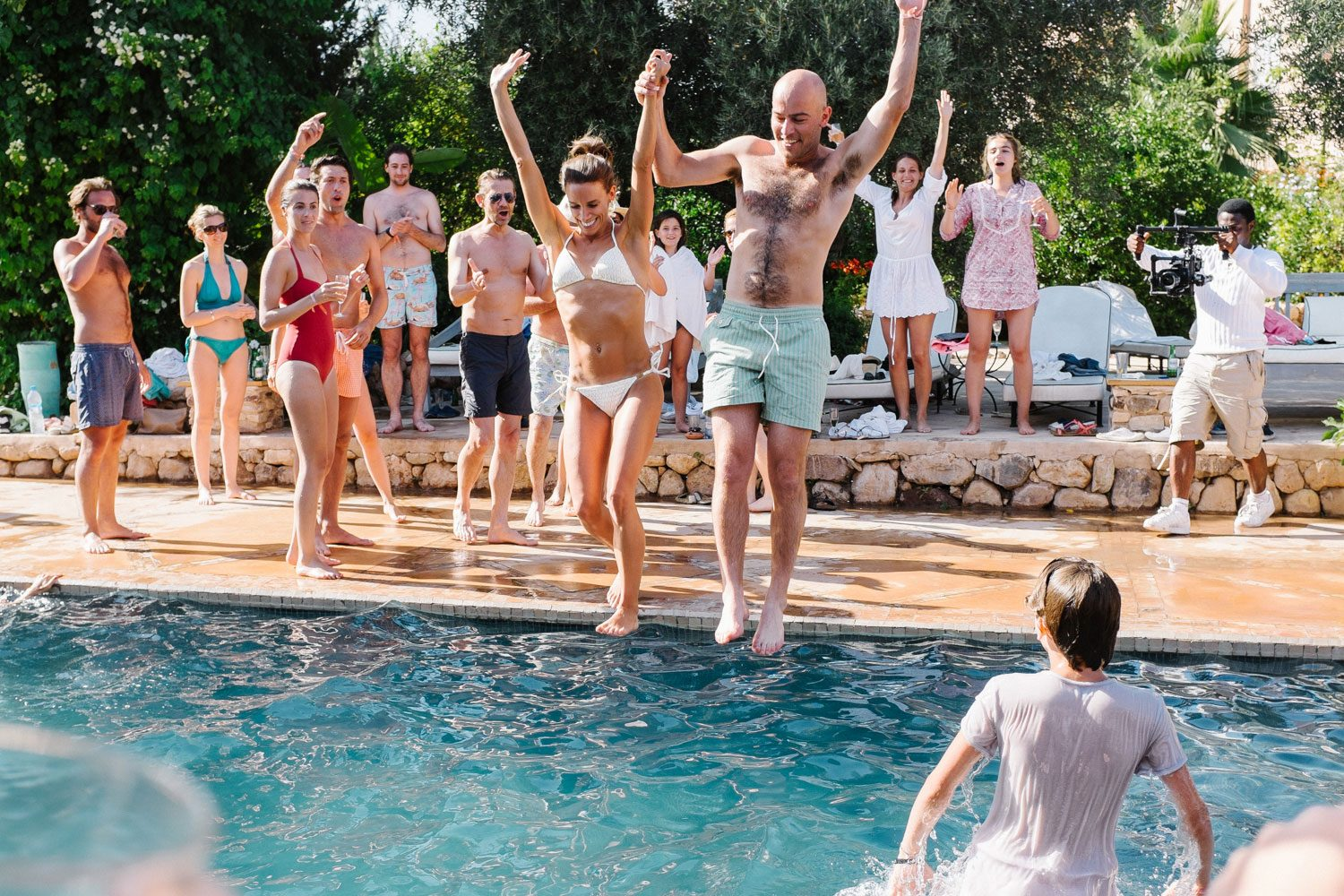 bride and groom jump into swimming pool