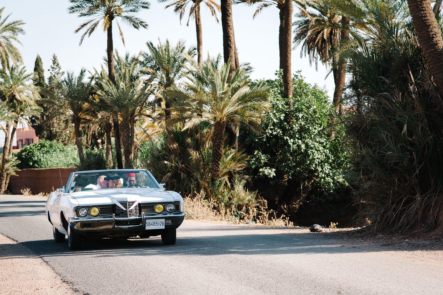 bride and groom arrive in open top car