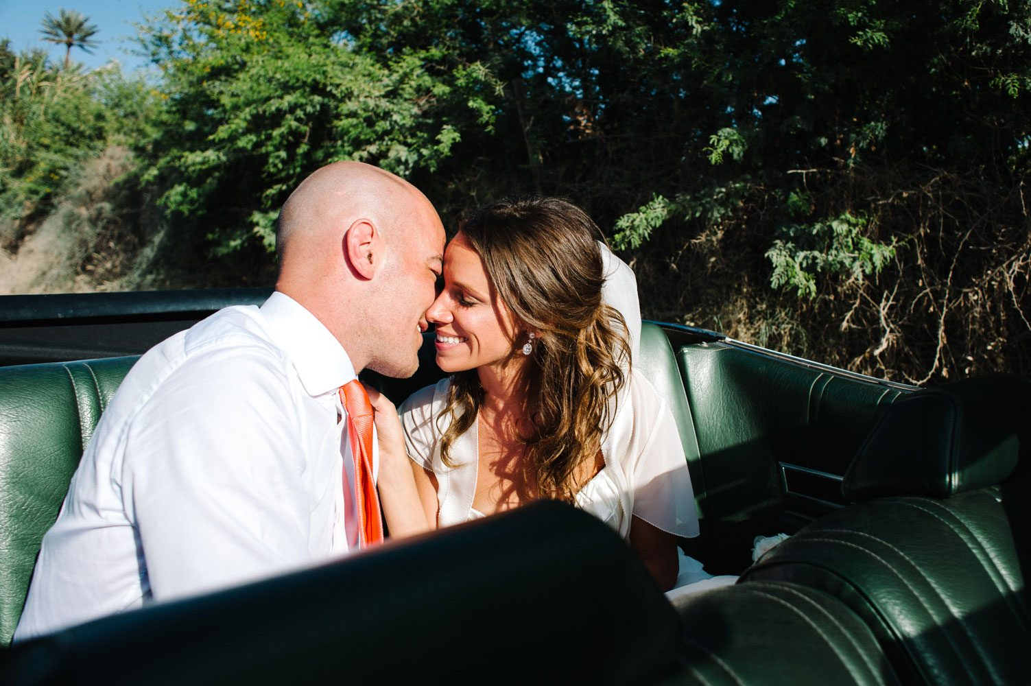 bride and groom kiss in back of car