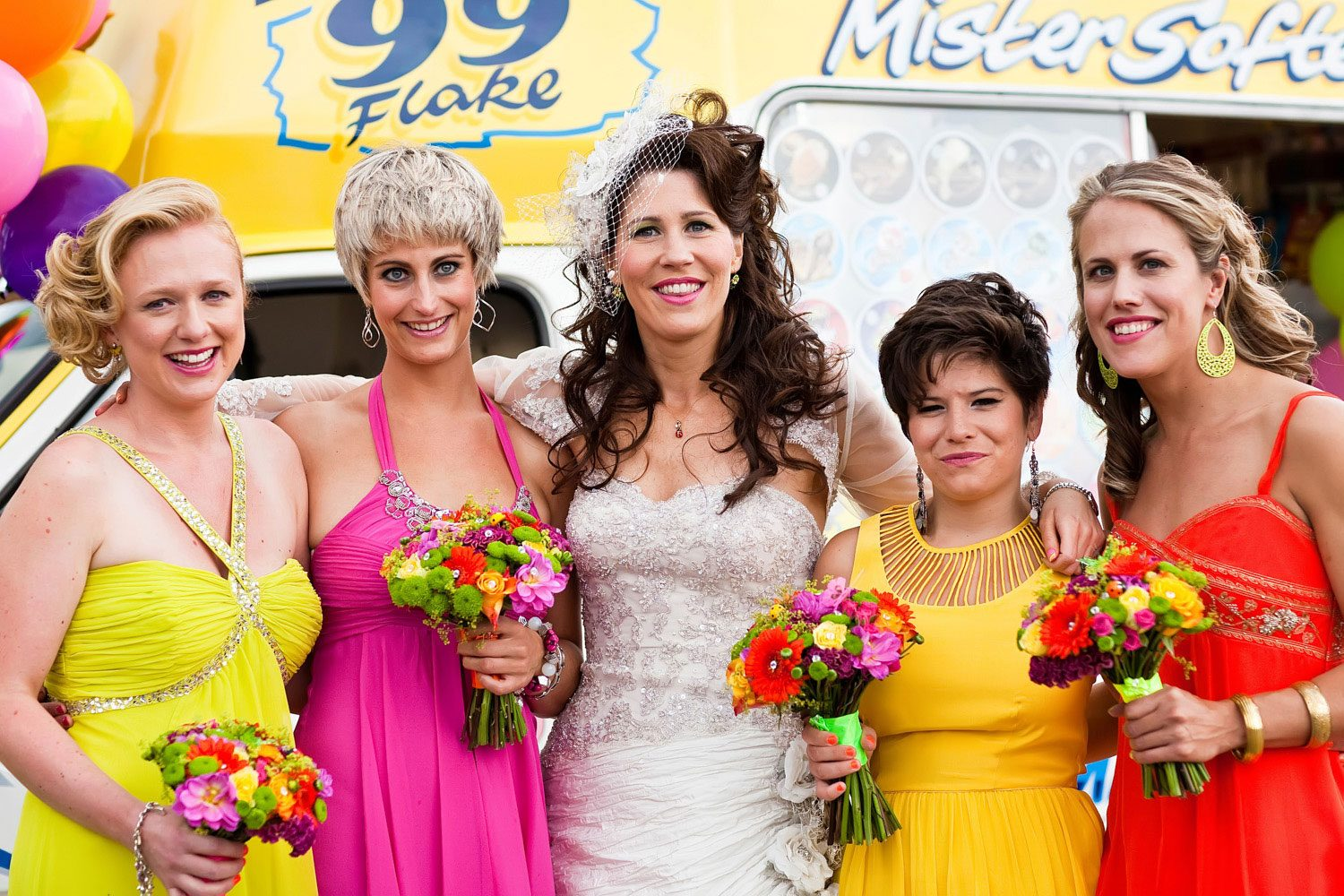 bride and bridesmaids pose in from of ice cream van
