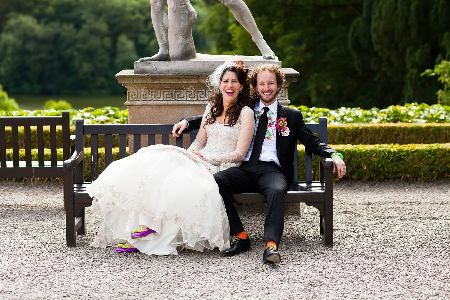bride and groom pose in bespoke wedding outfits