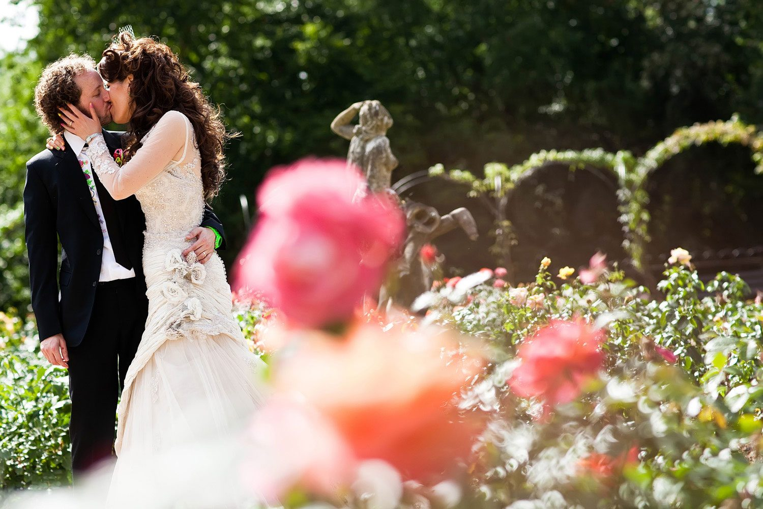 bride and groom kiss in front of wedding roses