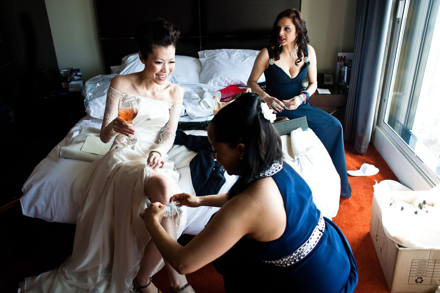 bridesmaids puts garter on bride