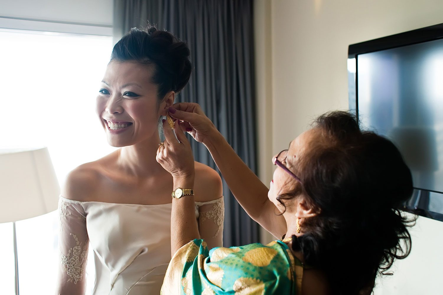 brides mother puts on earrings for bride
