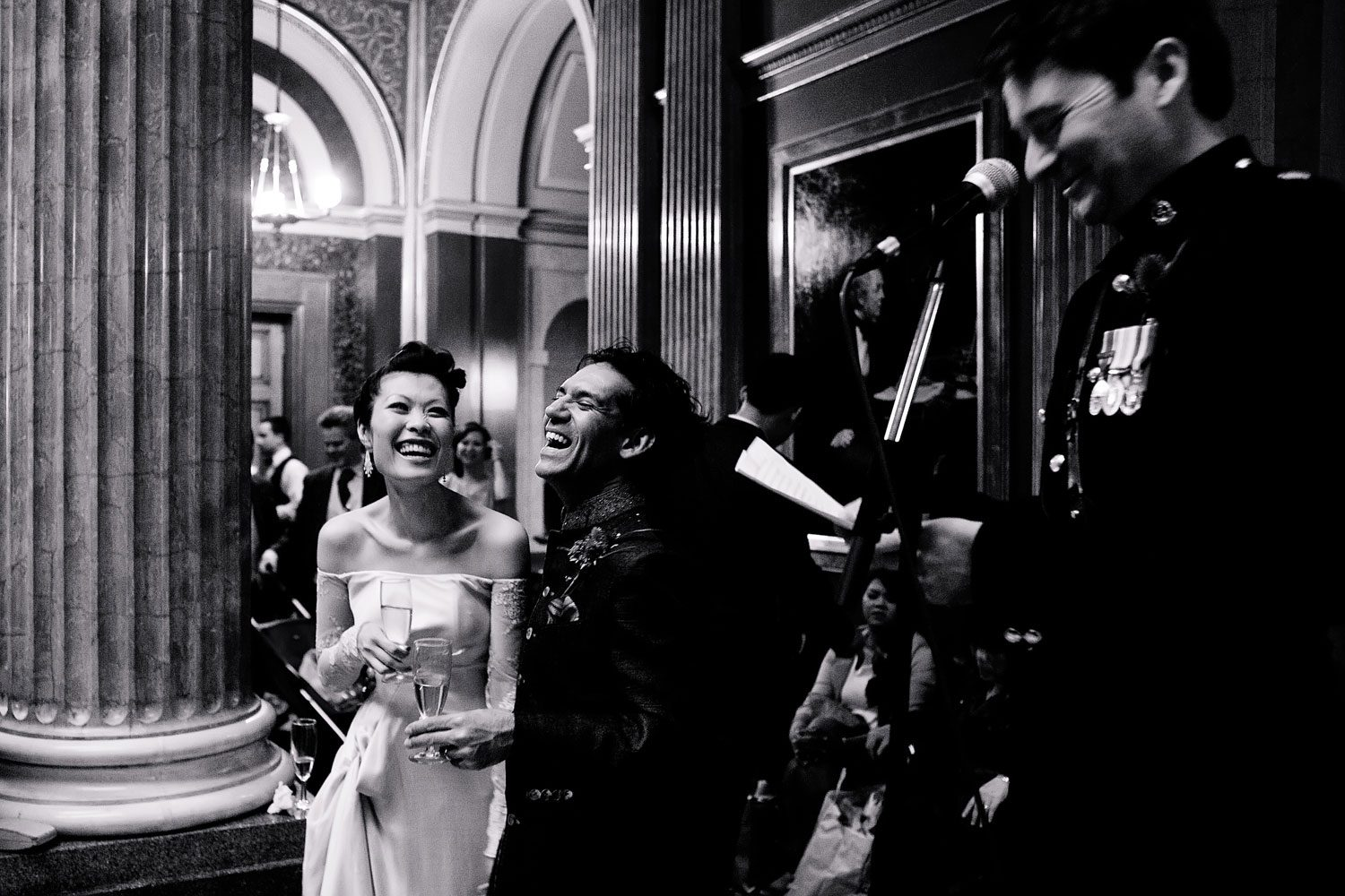 bride and groom laugh during speeches