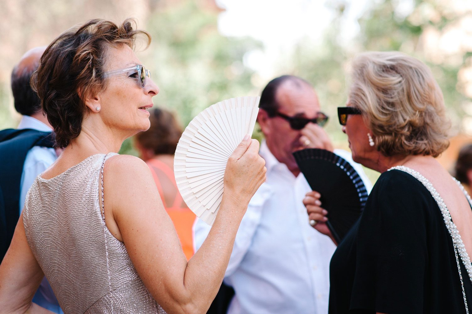 guests use wedding fans to keep cool