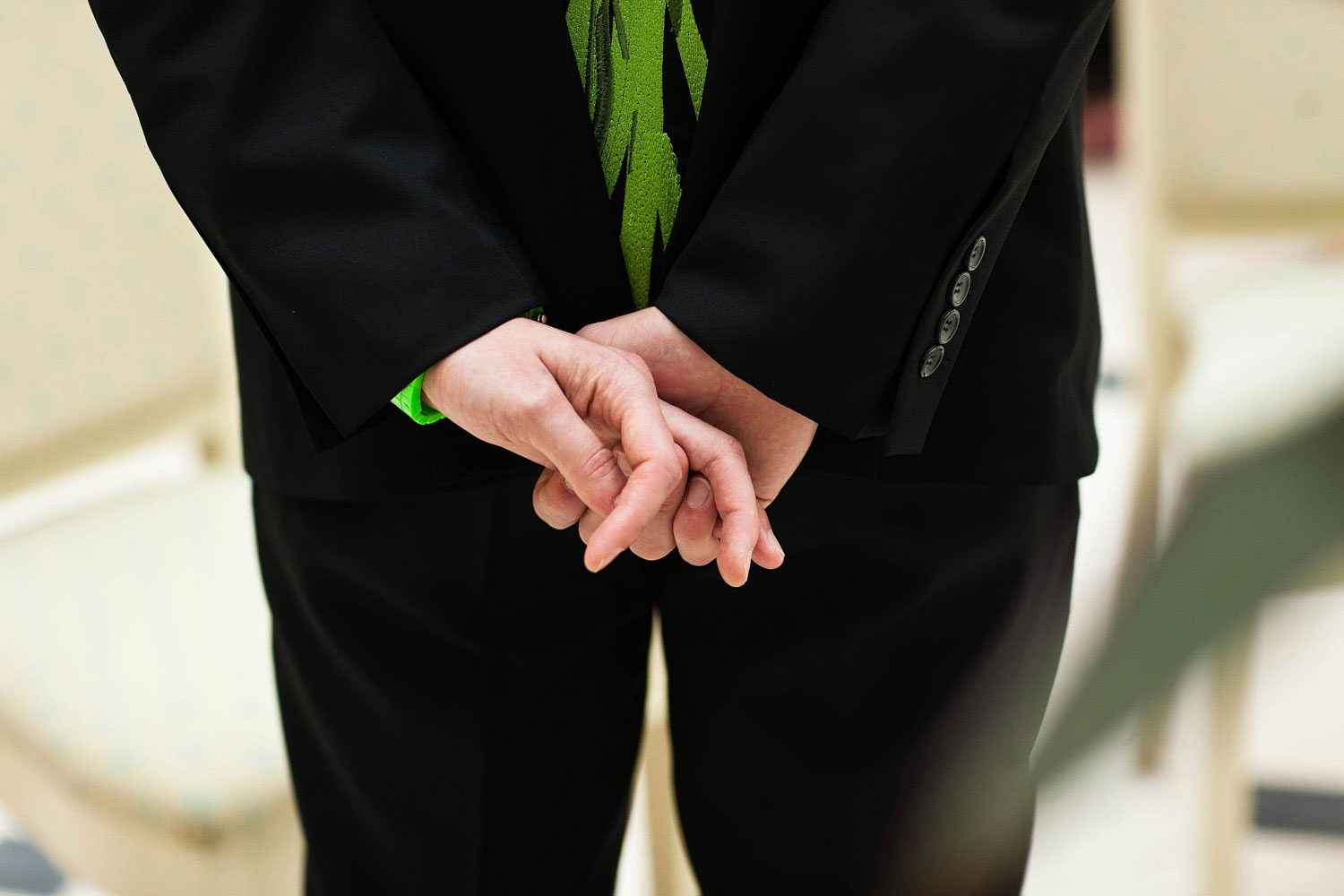 groom crosses fingers waiting for bride