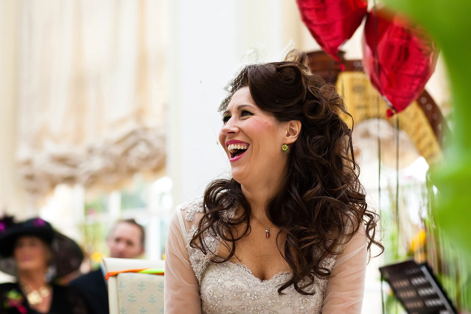 bride laughs surrounded by red helium balloons