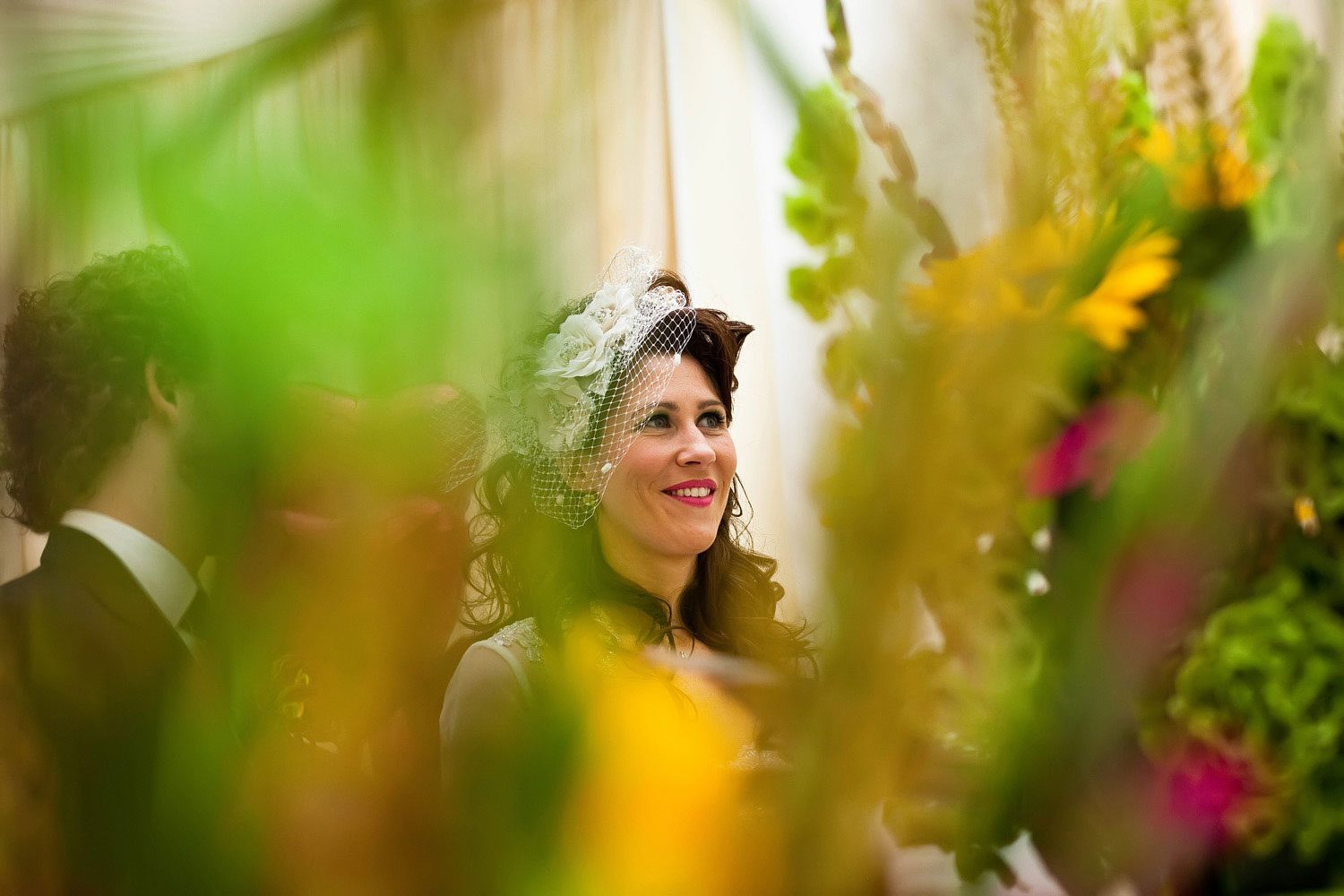 bride looks through wedding sunflowers