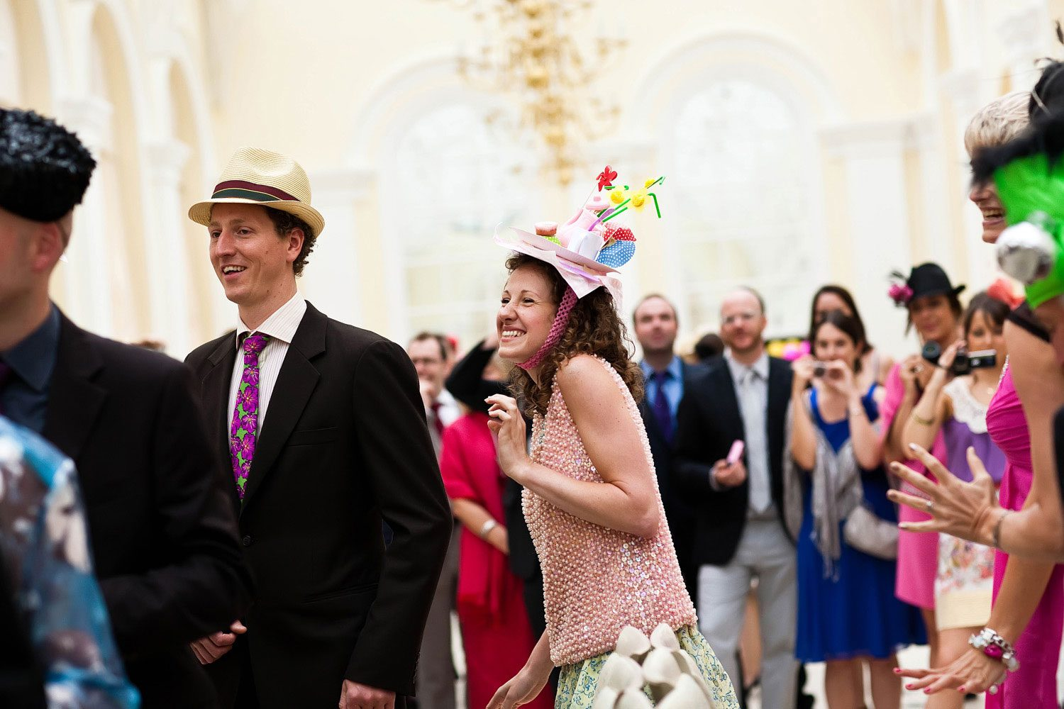 wedding guests dance in designer wedding hats