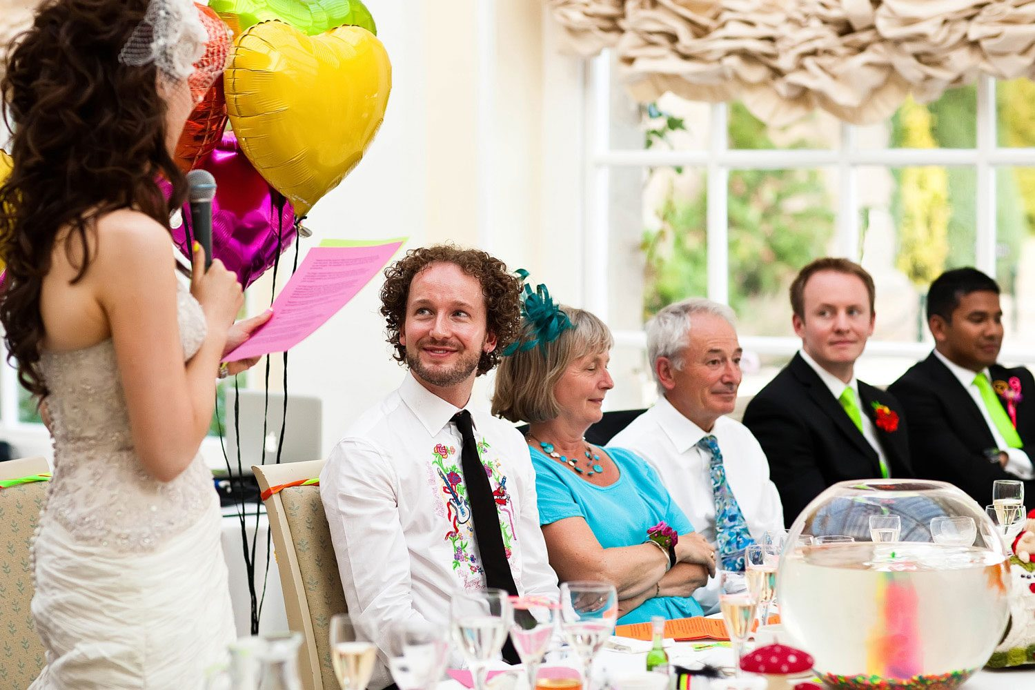 groom watches bride speaking at wedding