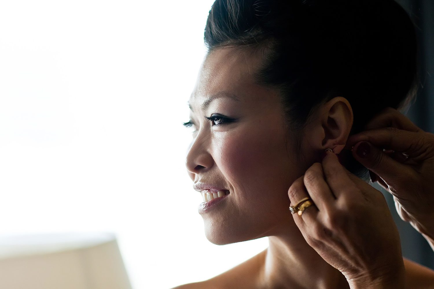 bride puts on earrings for london wedding
